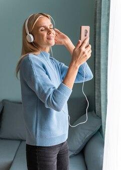 パンデミック時にスマートフォンでヘッドフォンで音楽を楽しんでいる自宅の女性