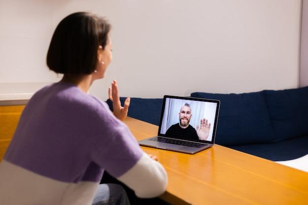 Женщина дома лицо время видео звонит своим друзьям мужу парню, болтает онлайн с ноутбука
