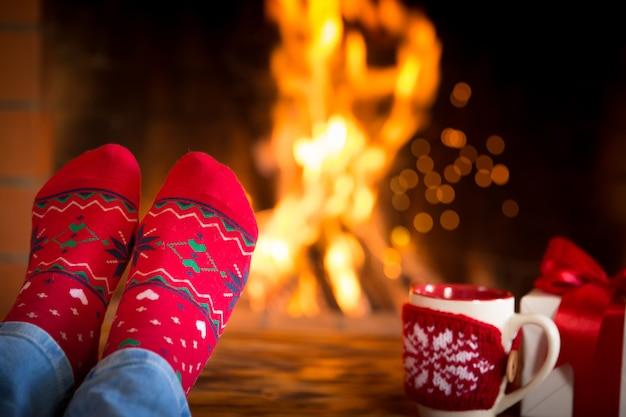 家にいる女性。暖炉のそばのクリスマスソックスの足。リラックスして快適。冬の休日のコンセプト