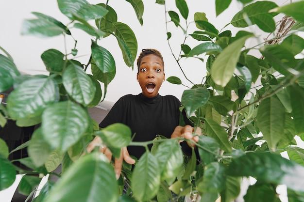 집에서 여자. 검은 스웨터에 소녀입니다. 사무실에서 아프리카 여자입니다. 화분을 가진 사람.