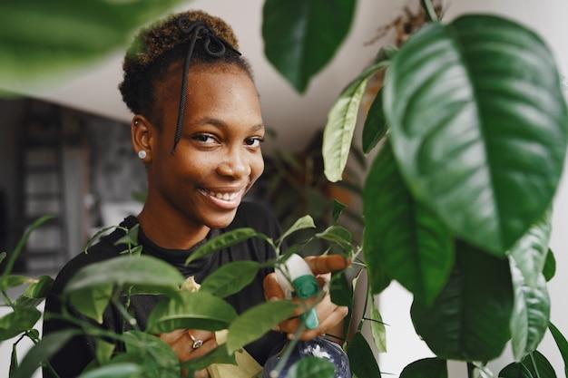 집에서 여자. 검은 스웨터에 소녀입니다. 아프리카 여자는 걸레를 사용합니다. 화분을 가진 사람.