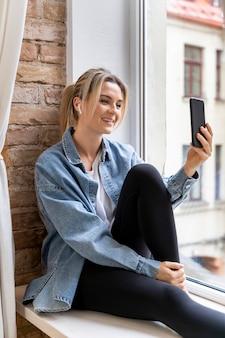 Женщина дома, имея видеозвонок с семьей