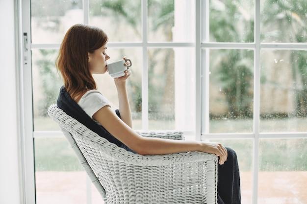 一杯のコーヒーステンドグラスの窓のインテリアとアームチェアで自宅で女性