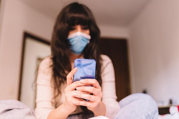 携帯電話を使用して彼女の顔に呼吸用呼吸マスクを自宅で使用する女性。パンデミックコロナウイルス、ウイルスcovid-19。隔離、感染防止のコンセプト。携帯電話に焦点を当てます。