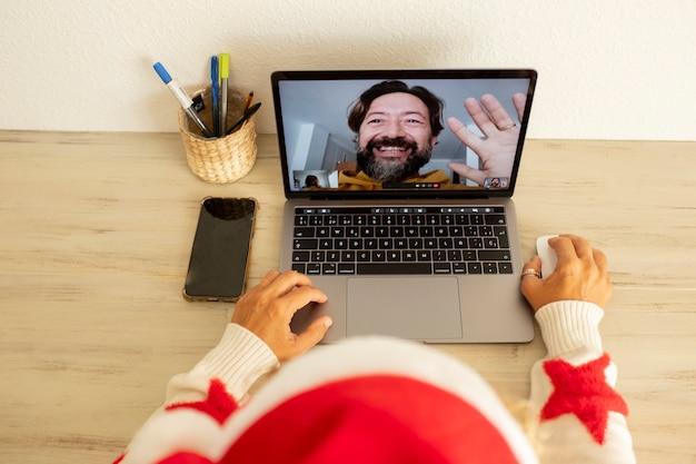 크리스마스 휴가에 집에 있는 여자는 노트북 컴퓨터를 사용하여 라인 화상 통화 통신을 통해 남자에게 전화를 걸고 있습니다. 축제 겨울 시즌의 사람과 통신 기술