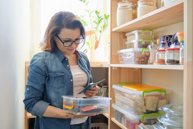 Женщина дома на кухне, возле деревянных полок с едой