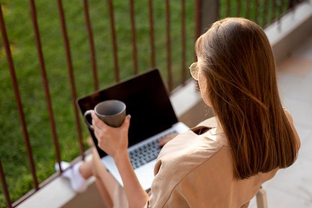 Женщина дома в карантине, работает с ноутбуком на открытом воздухе