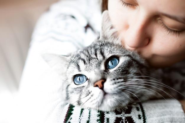 自宅で女性が彼女の素敵なフワフワした猫にキス