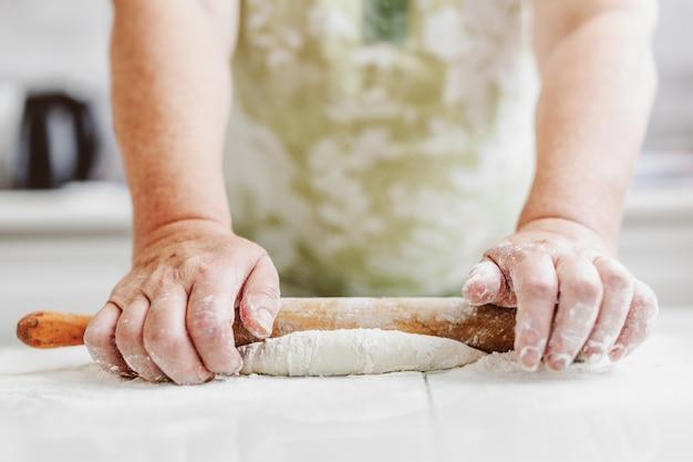 파스타 피자 또는 빵 요리를 위해 반죽을 반죽 집에서 여자. 가정 요리 개념. 생활 양식