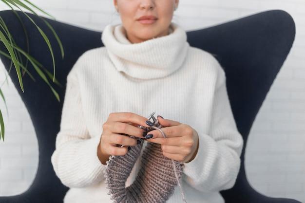 Женщина дома вязание крупным планом