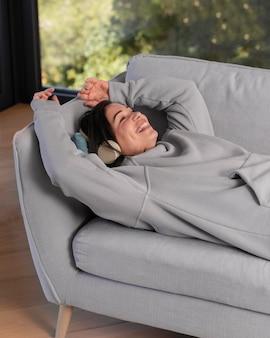 家で音楽を聴いている女性