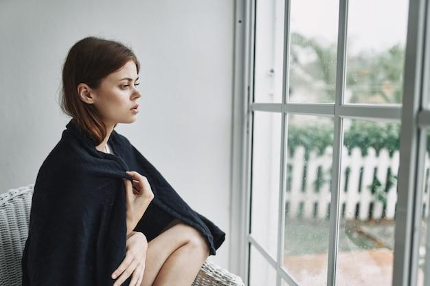 自宅の窓の近くの女性