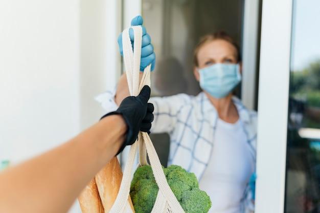 Женщина дома собирает свои продукты в самоизоляции