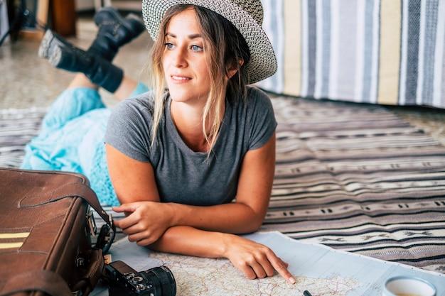 ガイドマップと笑顔を見て旅行休暇を計画している自宅の女性
