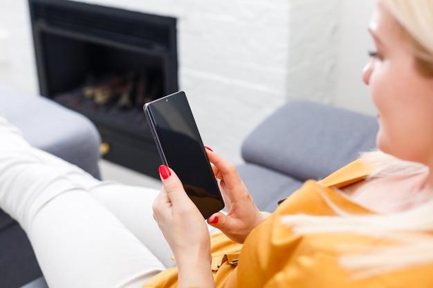 태블릿 컴퓨터 wi-fi 연결로 이메일을 읽는 소파 소파에서 집에 있는 여성
