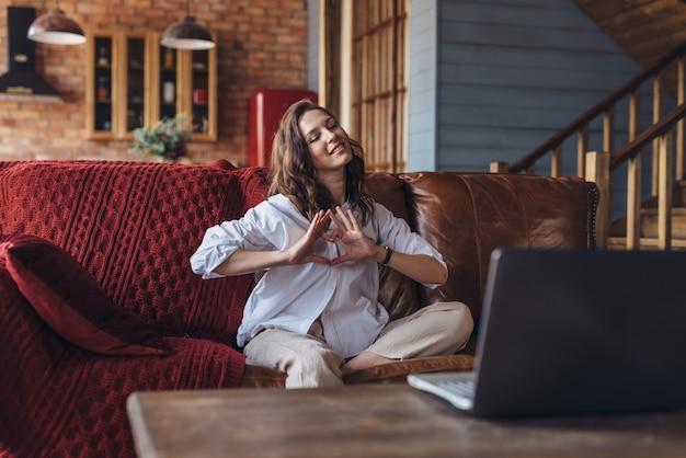 自宅の女性はビデオ通話で愛する人と話し、愛の象徴としてハートのジェスチャーを示します。