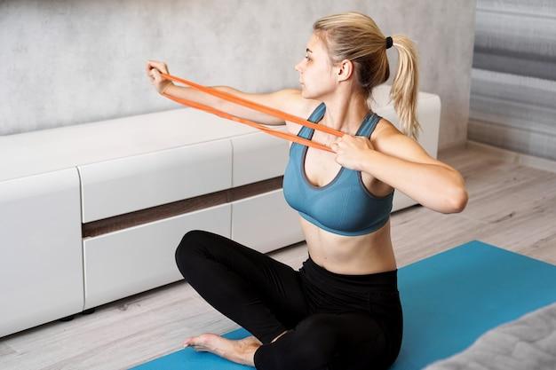집에서 체중 감량을 시도하고 그녀의 손에 탄성 밴드로 훈련을받는 여성