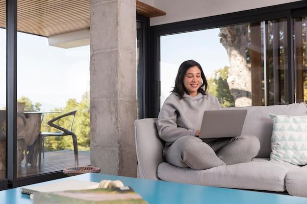 Женщина дома, используя ноутбук