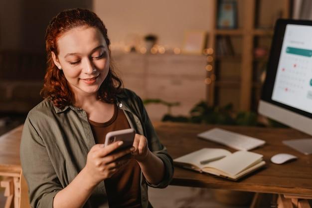 コンピューターの前でスマートフォンを使用して自宅で女性