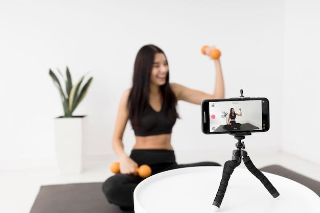 Женщина дома ведет видеоблог во время тренировки