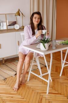彼女の机でコーヒーを飲みながら家にいる女性