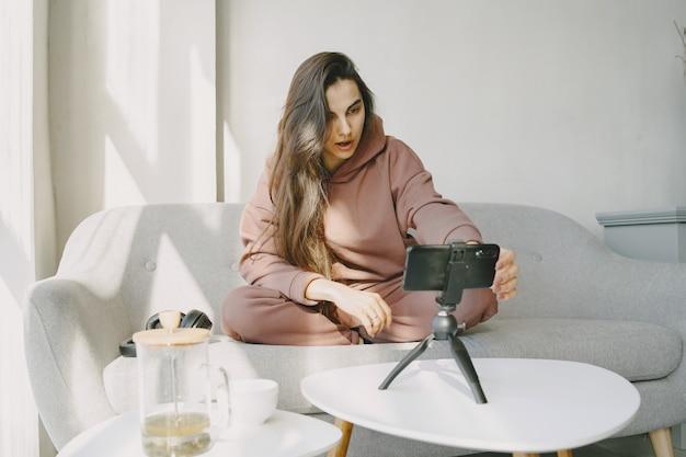 ヘッドフォンと電話を持っている自宅の女性がオンラインで通信します