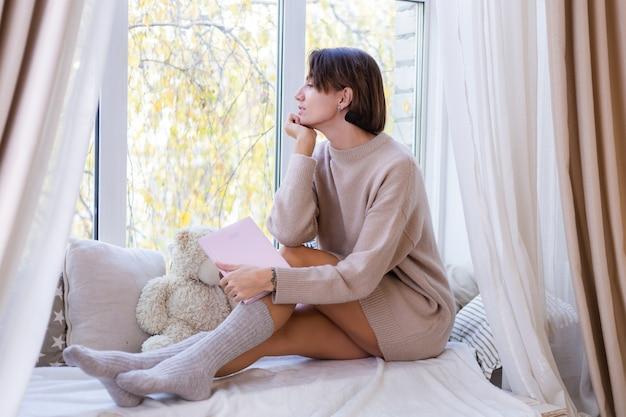 ノートを持って家にいる女性は、快適なセーターと暖かいウールの靴下、窓の外の冷たい外壁の窓辺に座っています