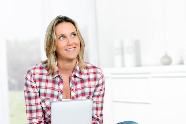 Женщина дома с планшетом, глядя на кого-то