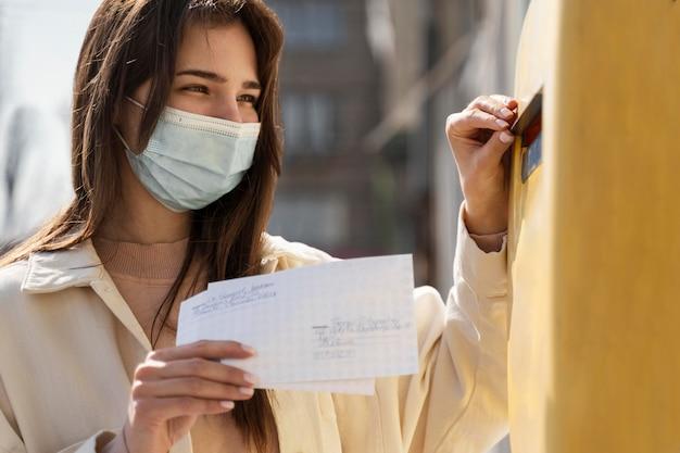 封筒とメールボックスで女性
