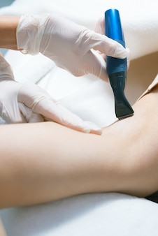 Женщина в салоне, имеющая процедуру удаления волос на подмышках