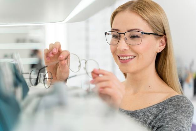 Женщина в магазине примеряет очки