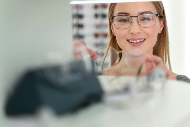 眼鏡をかけようとしている店の女性