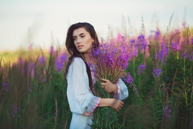 Женщина на закате в сиреневом поле.