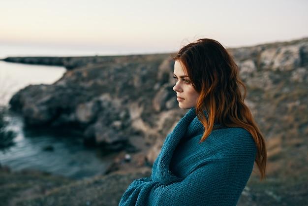 彼女の肩に毛布を持って山の海の近くで日没の女性