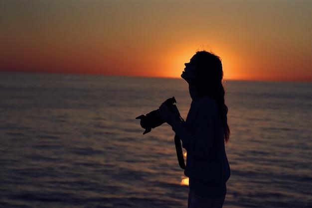 カメラを手に海の近くの日没の女性