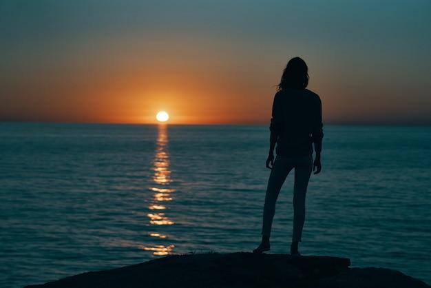 Женщина на закате море силуэт на берегу и пляжное небо
