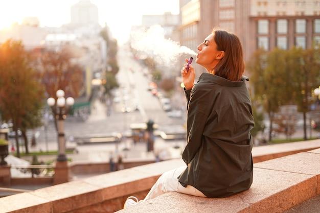 Женщина на закате с прекрасным видом на город, наслаждается теплыми днями, свободой, позитивными эмоциями, курит электронную сигарету