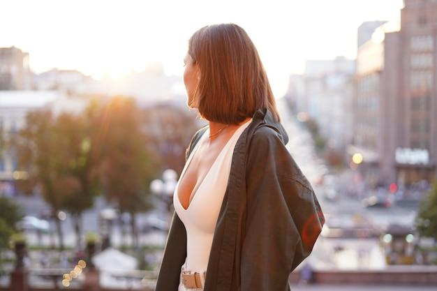 素晴らしい街の景色、暖かい日、自由、ポジティブな雰囲気を楽しんでいる日没の女性