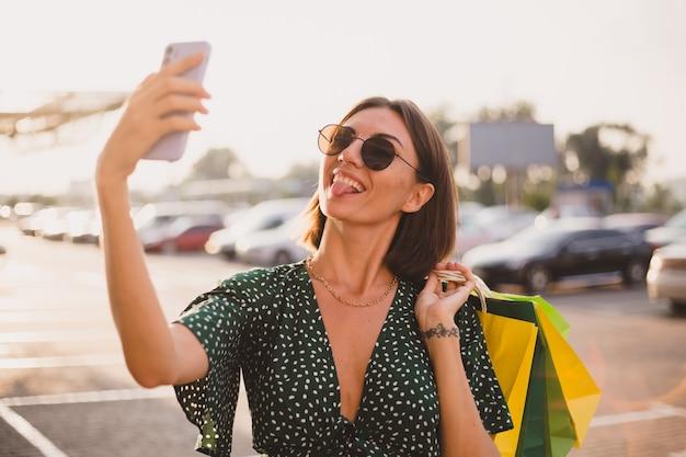 휴대폰으로 행복한 쇼핑몰 옆에 다채로운 쇼핑백과 주차장이 있는 일몰의 여성이 셀카를 찍는다