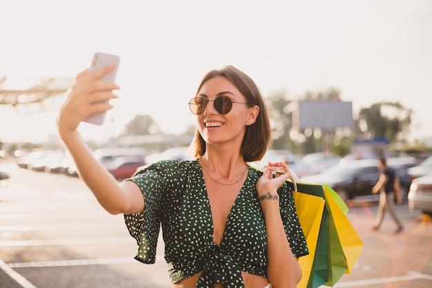 Женщина на закате с красочными сумками и автостоянкой у торгового центра счастлива с мобильным телефоном, фотографирует селфи
