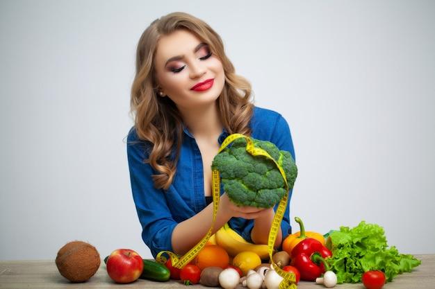 果物と野菜のブロッコリーを保持しているテーブルで女性