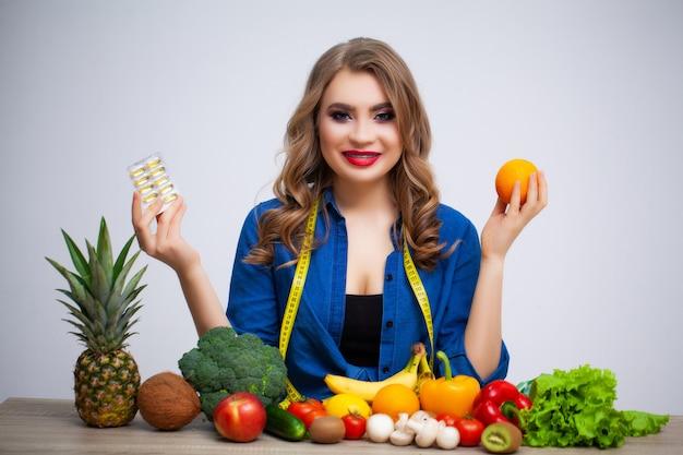 Женщина за столом держит апельсин и таблетки на фрукты и овощи