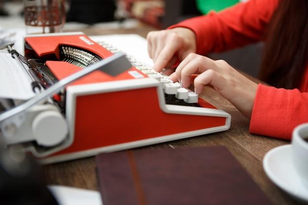 Женщина за столом печатает на пишущей машинке