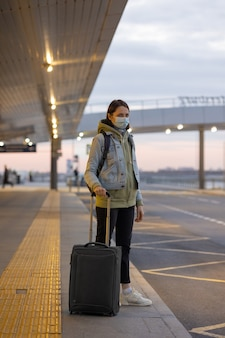 空港の到着時と出発時にタクシーを呼ぶタクシーを捕まえる空港の女性