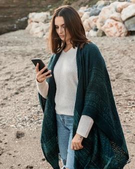 Женщина на пляже с помощью смартфона