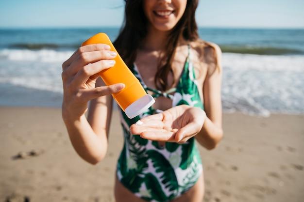 Suncream와 함께 해변에서 여자