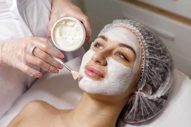 미용사의 여자는 얼굴에 마스크를 만든다