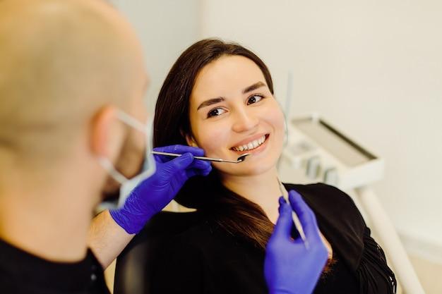 歯科医の診察を受けている女性