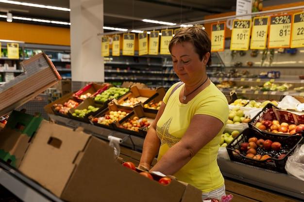 食料品店の女性は果物と野菜を選びます。