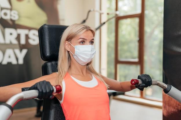 Женщина в тренажерном зале делает упражнения медицинскую маску